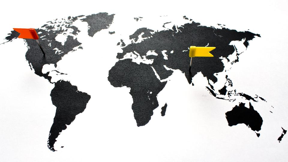 A map of the world with a red pin on the U.S and a yellow pin on India