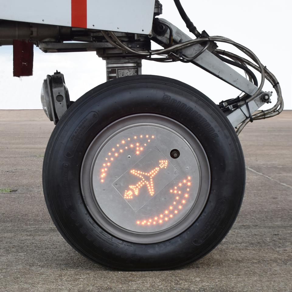 Aircraft nose wheel with lit aircraft indicator.