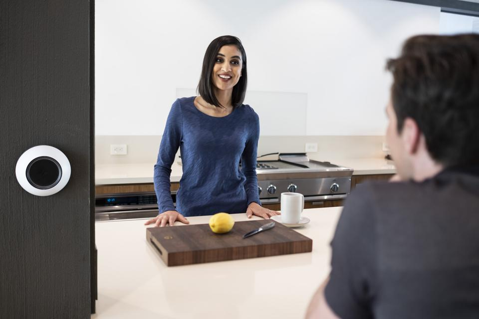 Couple in kitchen with smart home technology controller.