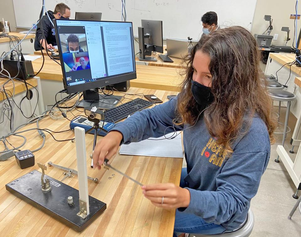 A female college student using lab equipment in class while virtual attendees watch.