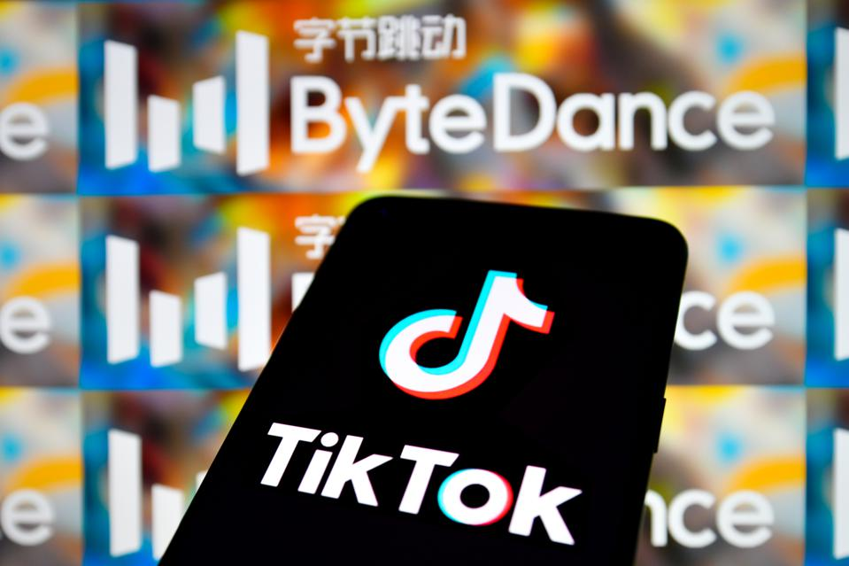 TikTok logo seen displayed on smartphone screen, against a backdrop showing ByteDance logo
