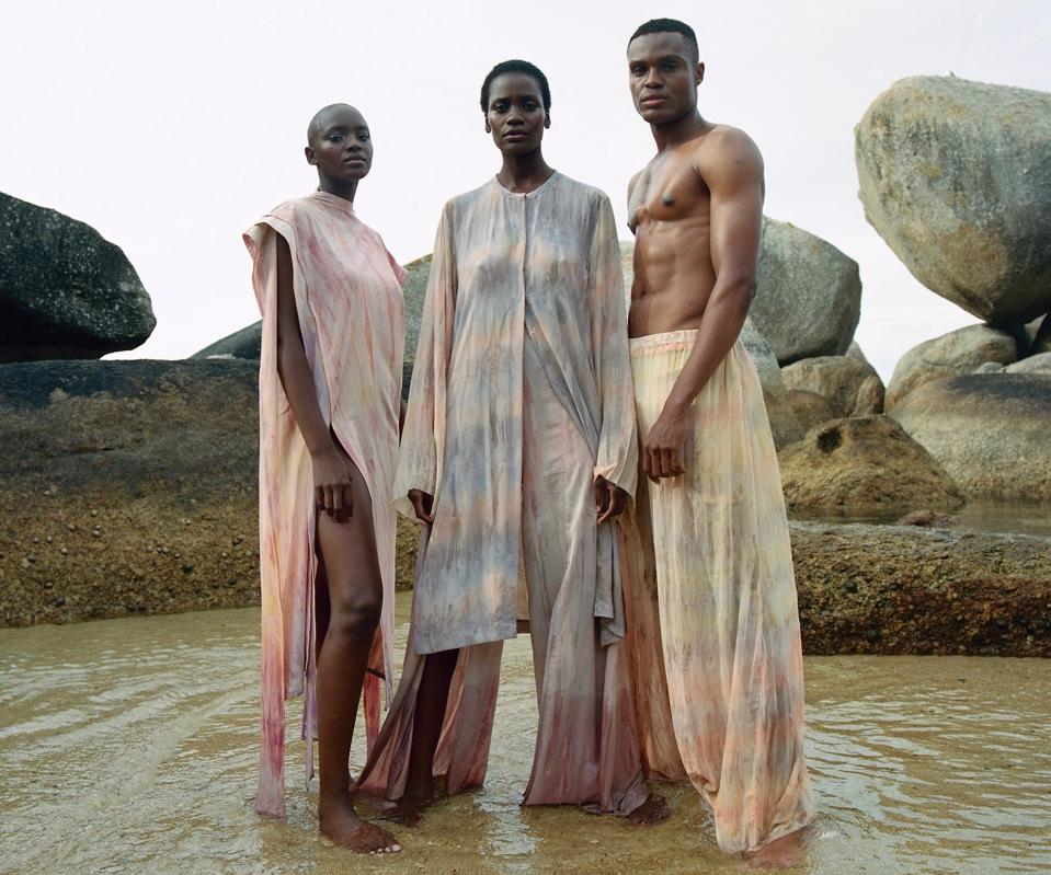 Two Black female models and one Black male model standing in a shallow pond against a large rock background modeling a tie-dyed clothing collection