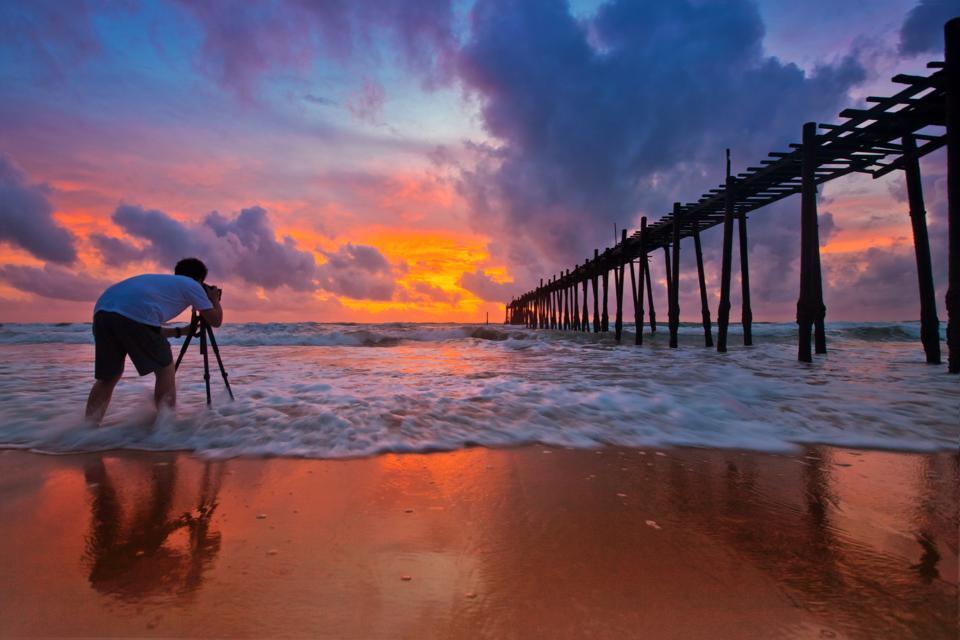 Photographer shooting sunset at beach.