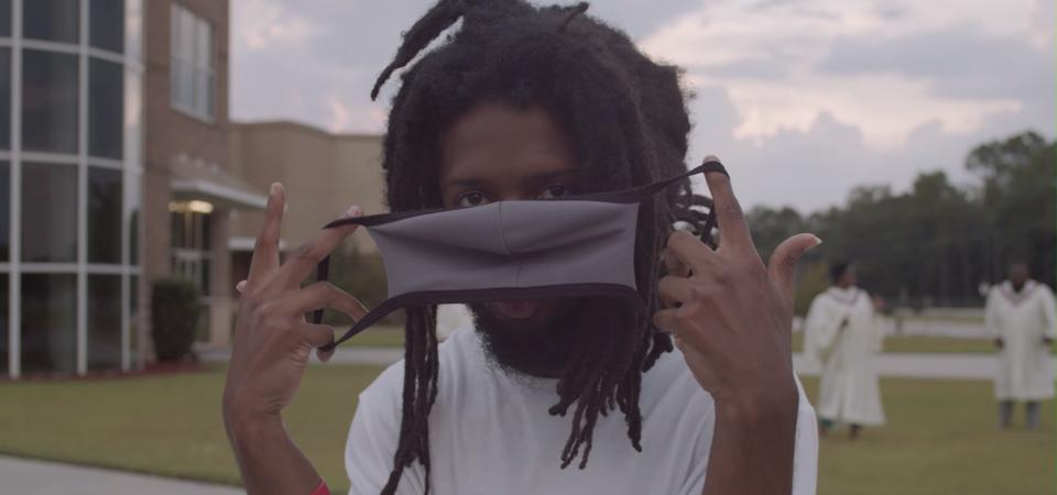 A still from Rapper Cantrell's music video First To Know - Cantrell holds a face mask