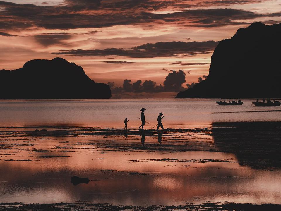 At sunset an old man, a middle-aged man, and his daughter walking in a beach in the Philippines