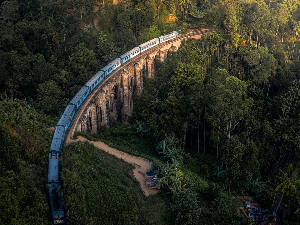 one of the iconic blue trains through the lush countryside in Sri Lanka.