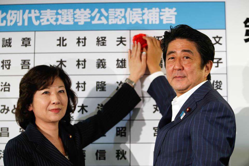 Shinzo Abe and Seiko Noda place a rosette on the board of candidates' names at the party headquarters in Japan.