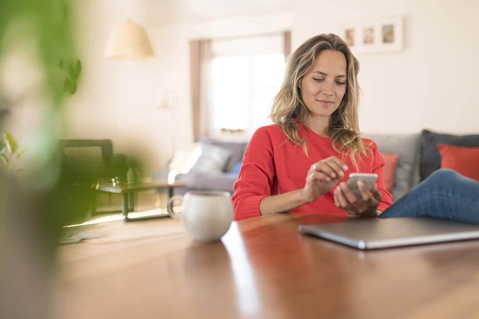 Woman using cell phone on dining table at home