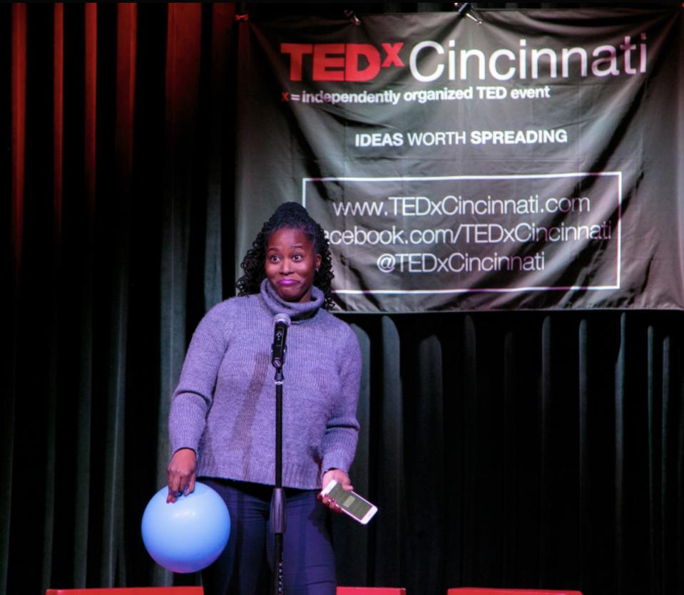 Dr. Bowden in a purple top with a ball and phone at Tedx