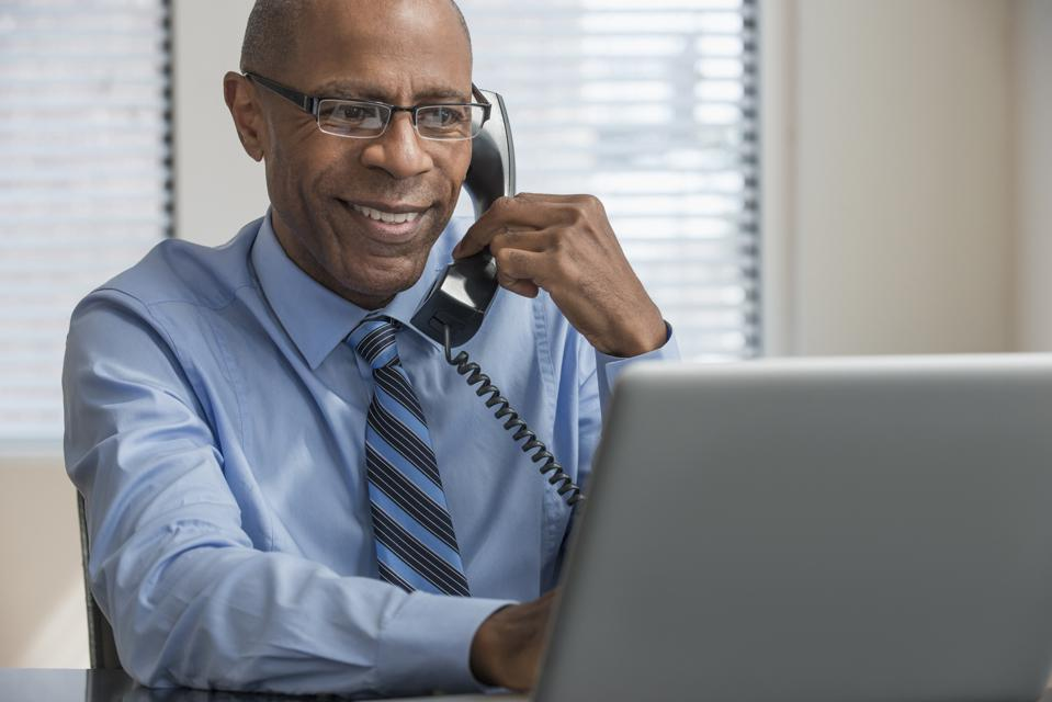 Black businessman on telephone using laptop in office