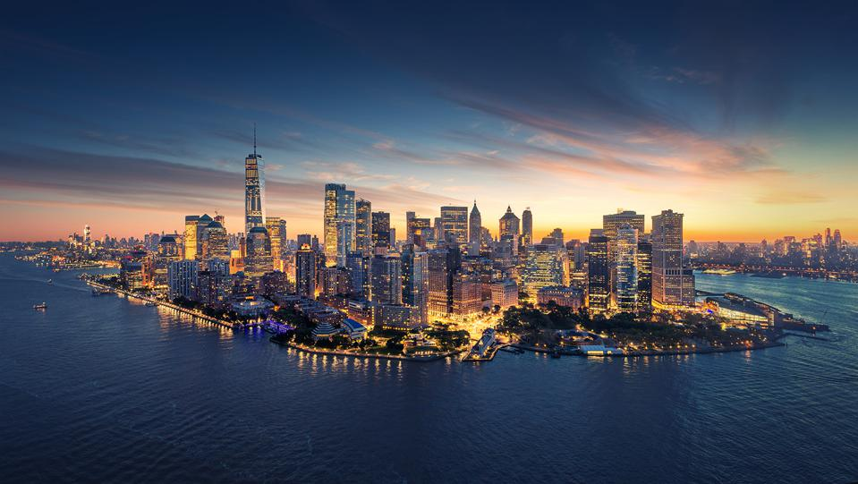 Lower Manhattan lit up at night with sunset in background.