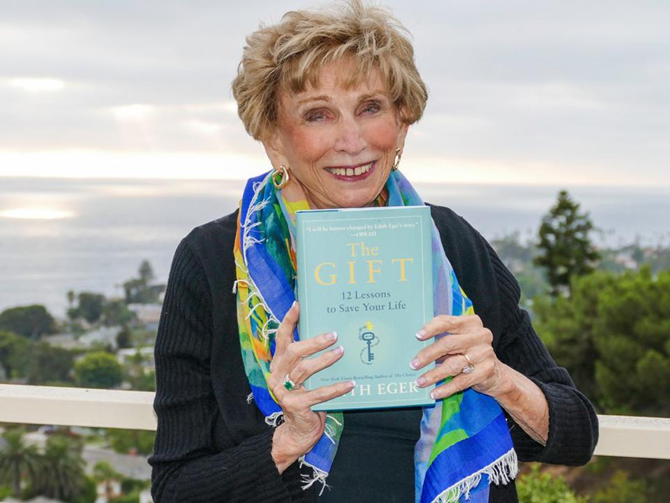 Dr. Edith Eger poses with her new book, The Gift: 12 Lessons to Save Your Life