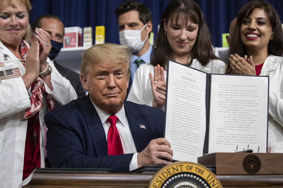 President Trump holds up a signed executive order on lowering drug prices.
