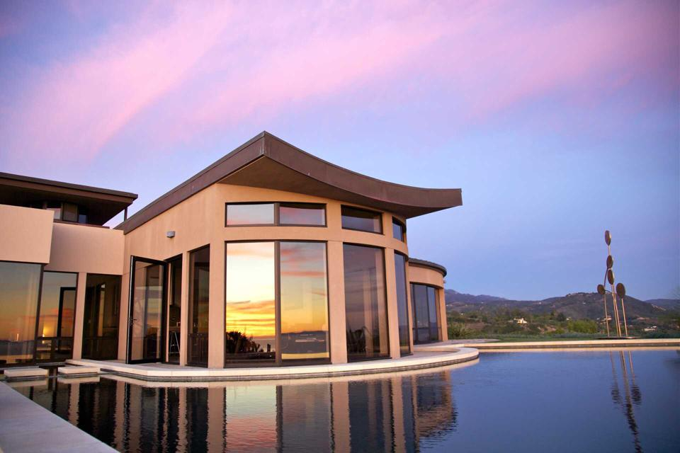 A modern home with many windows overlooking a pool.