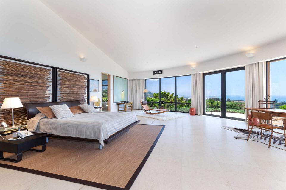 A spacious master bedroom with views over the ocean and hillside.