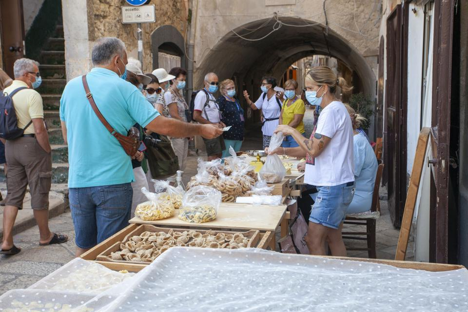 tourists in old town in Bari, Italy buying orecchiette pasta.