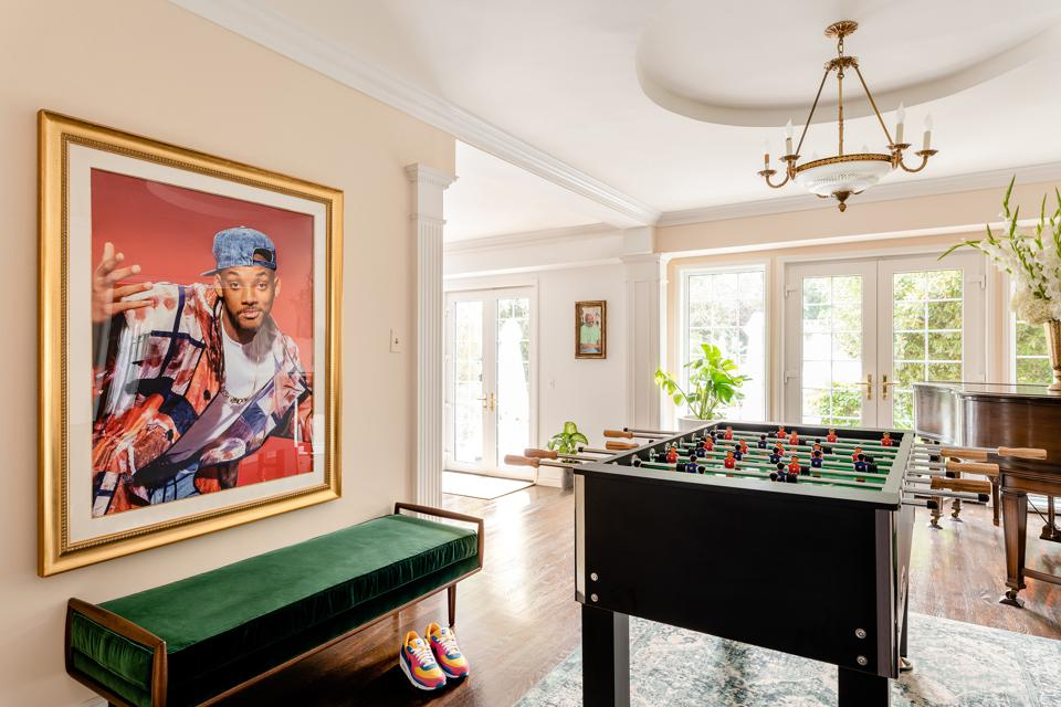 A portrait of Will Smith hangs over a foosball table inside of a mansion.