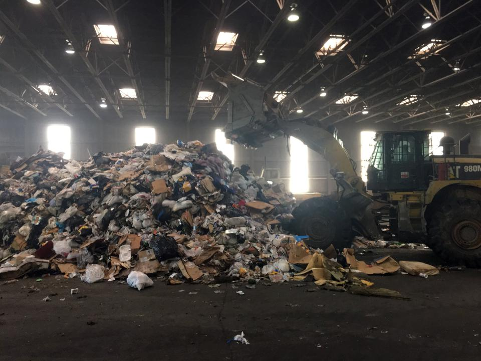 trash including recyclables piled at transfer station