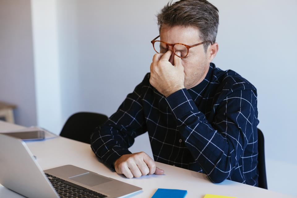 Businessman at desk in office rubbing his eyes