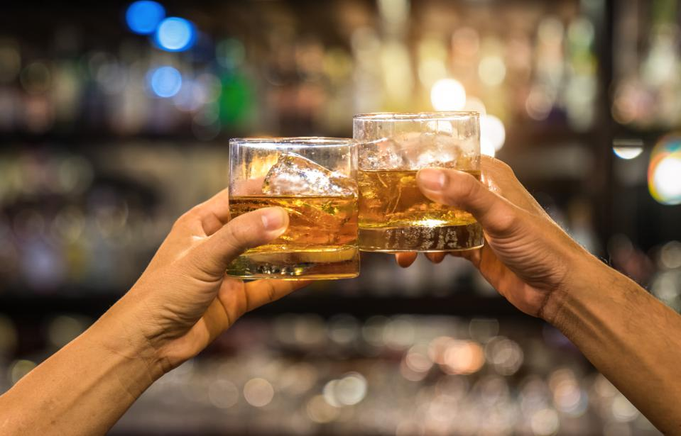 Two men clinking glasses of whiskey drink alcohol beverage together