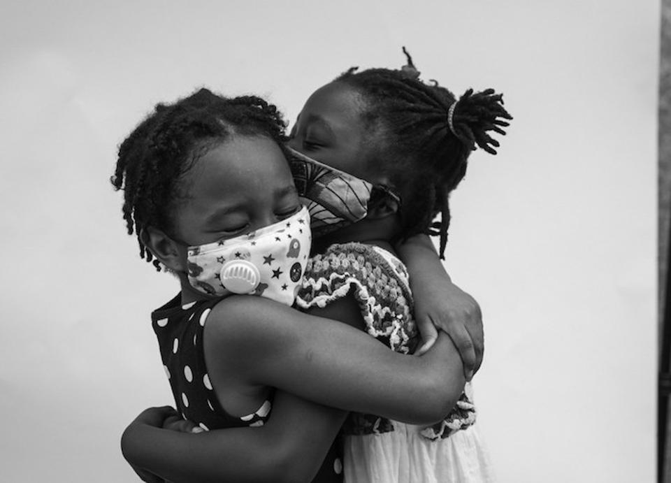 In June 2020, friends Kennedy (left) and Amina embrace at a children's march in support of the Black Lives Matter movement outside the Brooklyn Public Library in Brooklyn, New York.