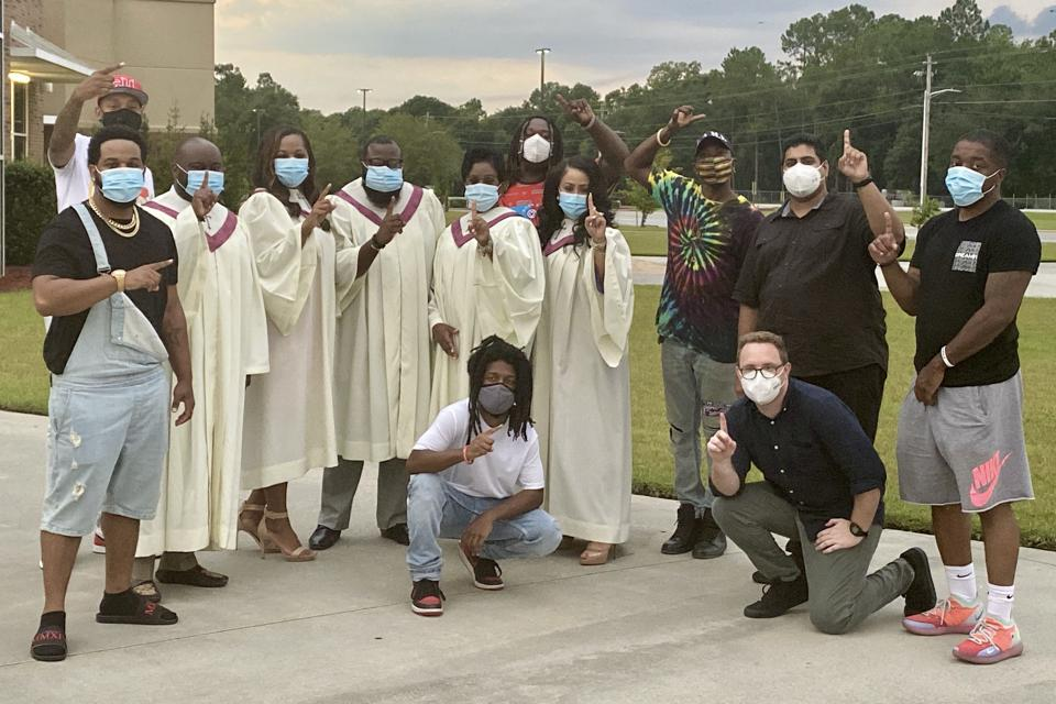 The producers, rappers and gospel singers of the First To Know video pose for a photo