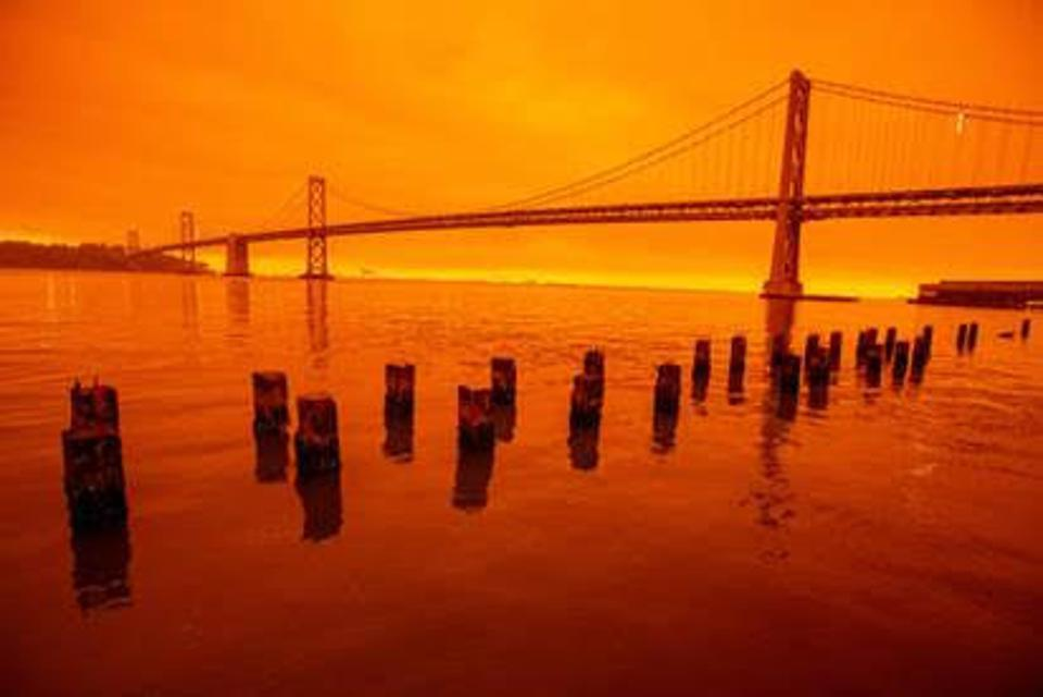 San Francisco's Golden Gate Bridge against a backdrop of fiery orange sky