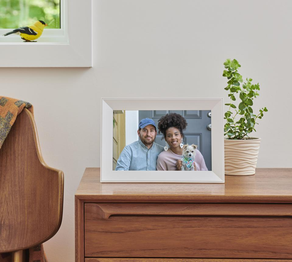 Aura's Carver frame containing a photo on a mid-century desk and clutter-free workspace