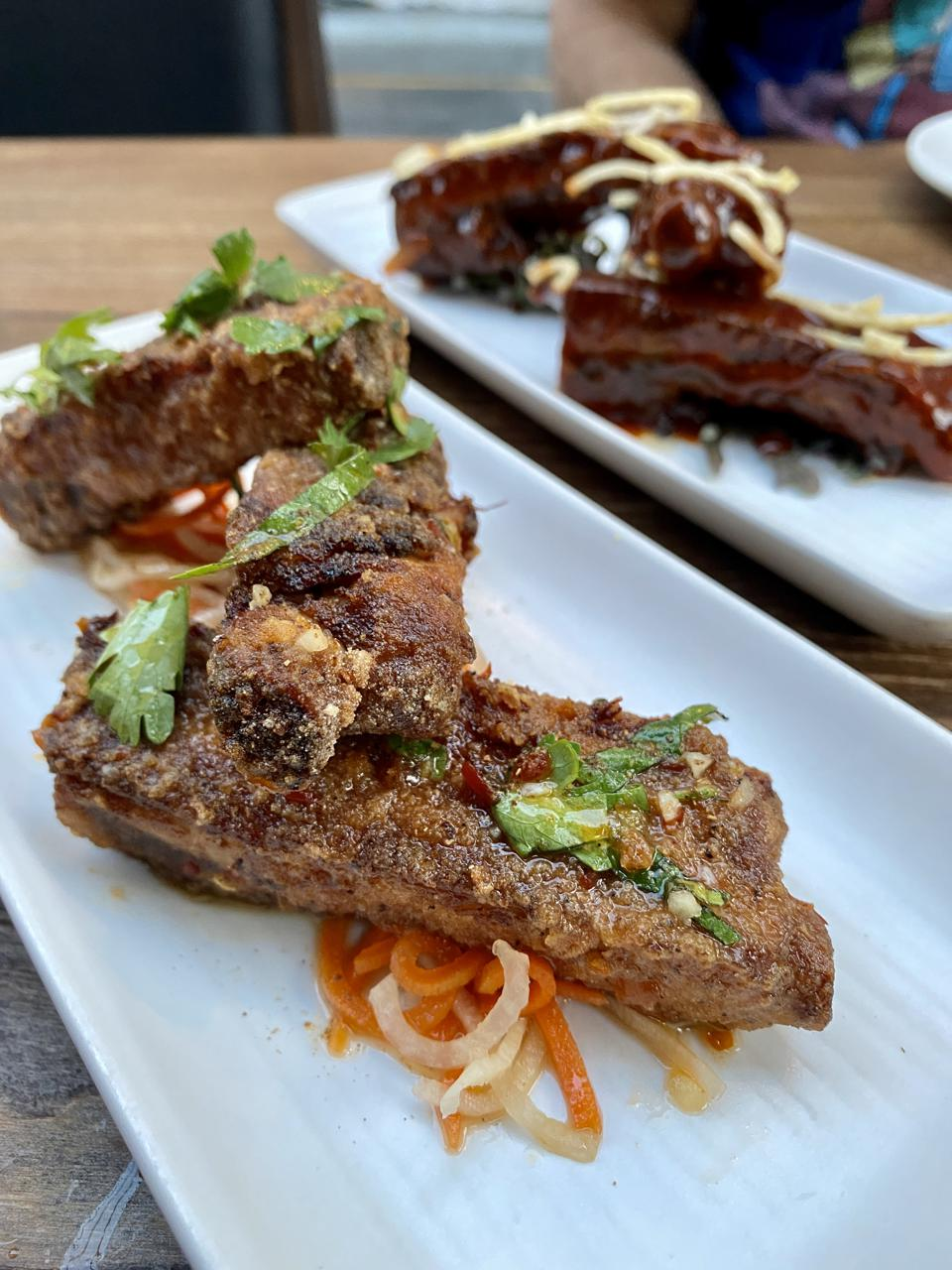 Dry fried Vietnamese ribs with preserved orange nuoc cham, fresh herbs, pickled carrots, Vietnamese seven spice.