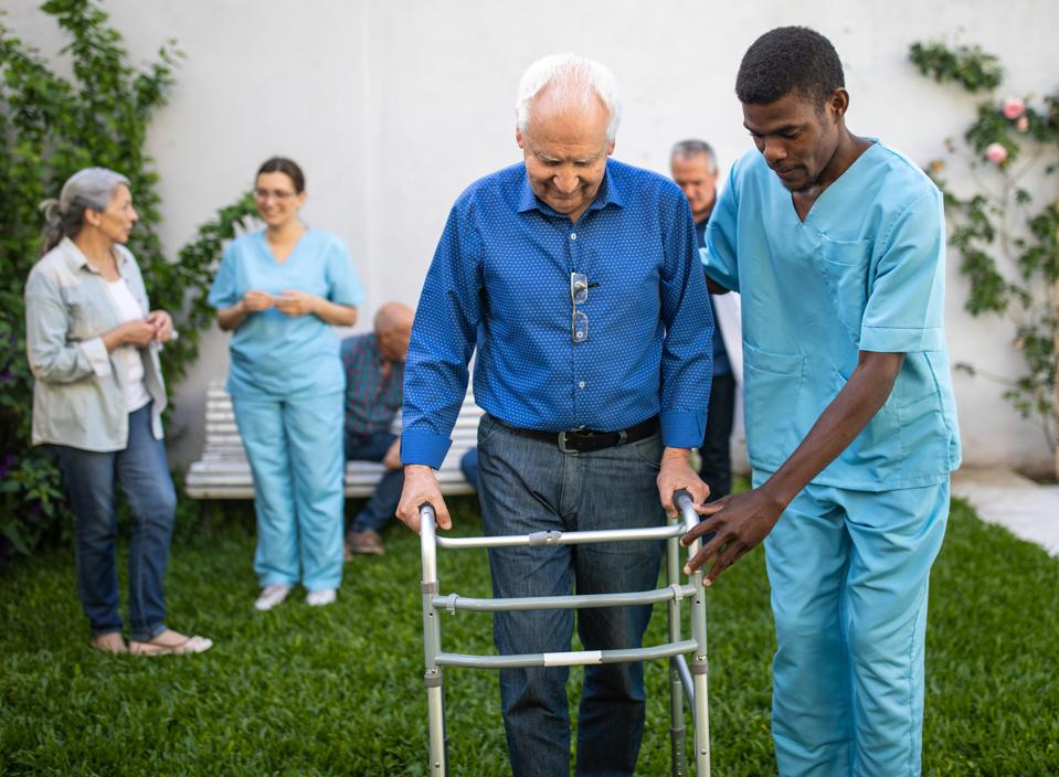 Black Male nurse helping senior man with mobility walker outdoor on beautiful day in backyard of nursing home