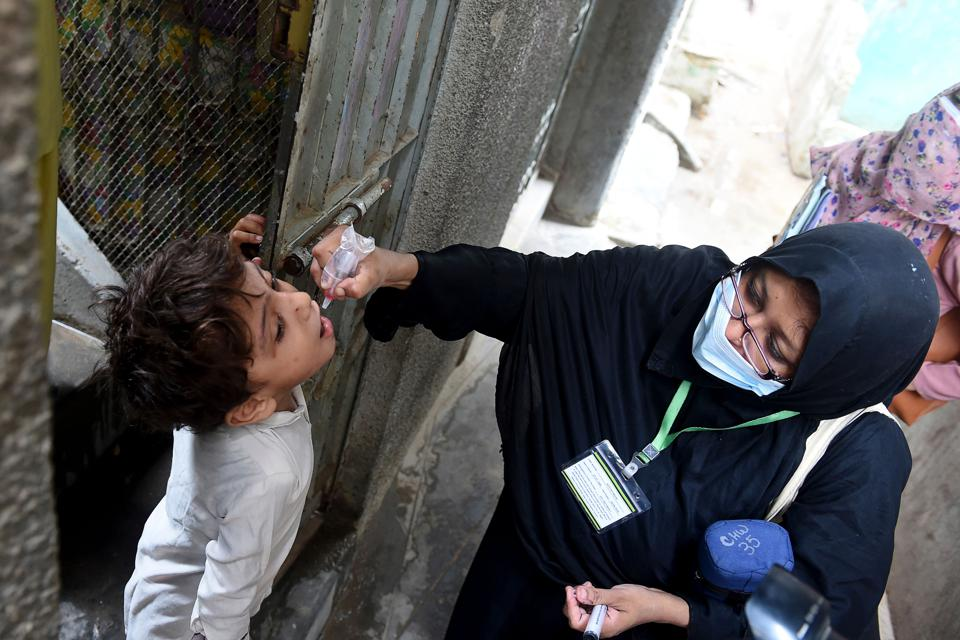 Woman wearing mask and headscarf puts drops in the mouth of a small boy