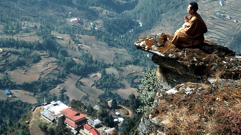 Tibetan doctor Sherab Barma meditates on a rocky outcrop above Chiwong Monastery