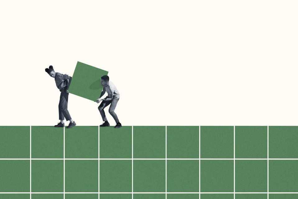 Woman and man carrying large green block on grid