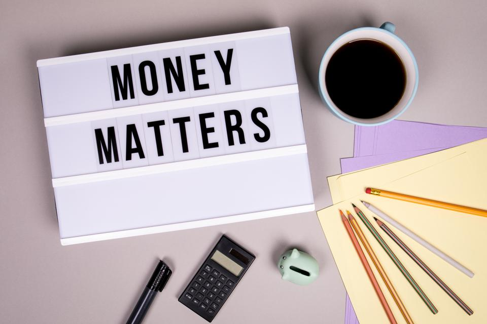 Money Matters written in black letters on a white box on a desk with coffee, calculator.