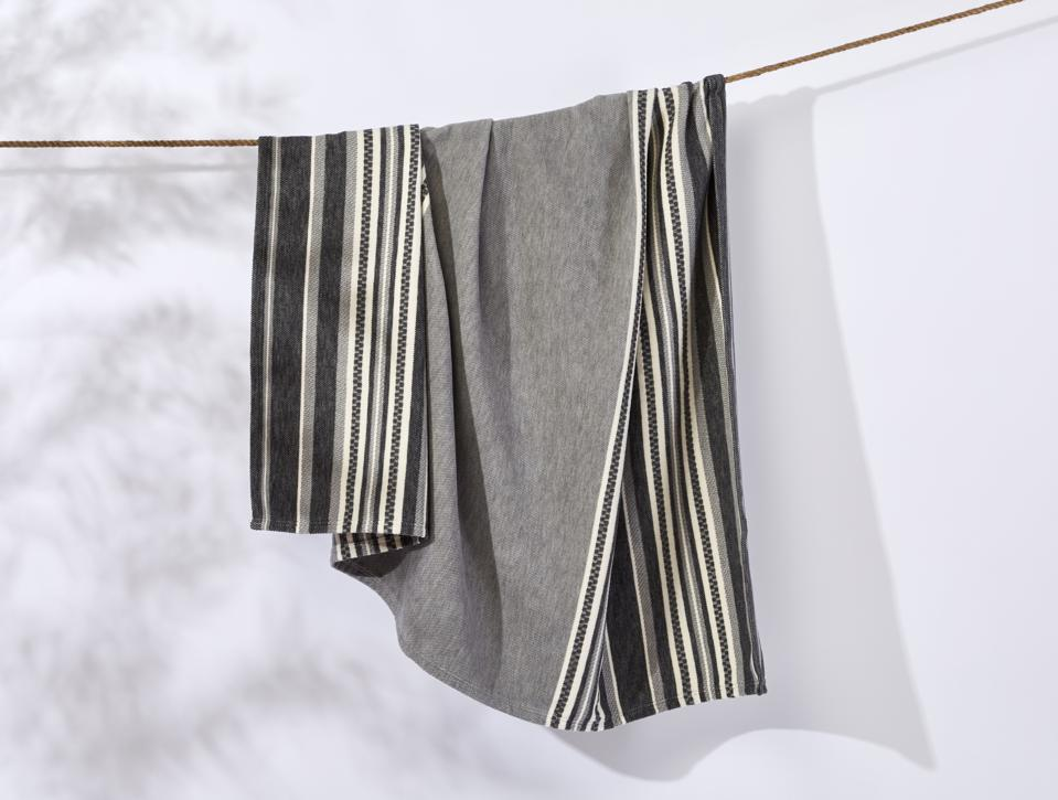 A striped soft organic cotton blanket in light gray, white and dark gray.