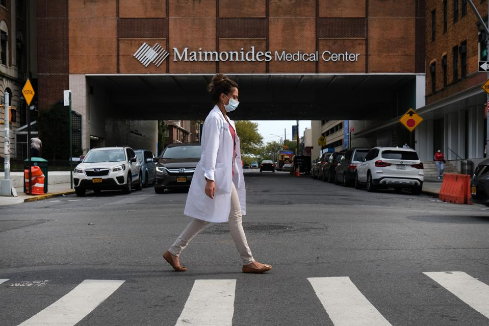 A medical work walks by a hospital in New York City.