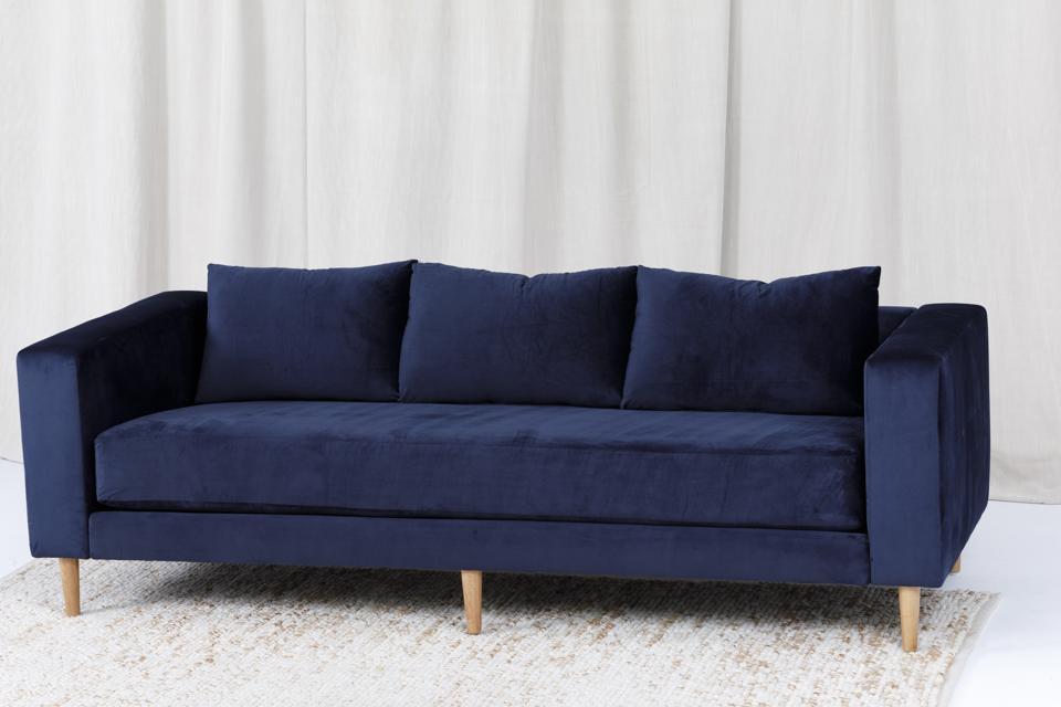 An indigo-colored velvet sofa.