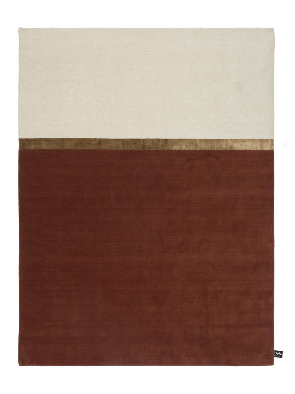 A hand-loomed rug in wool with a color-blocked pattern, one side off-white and rust.