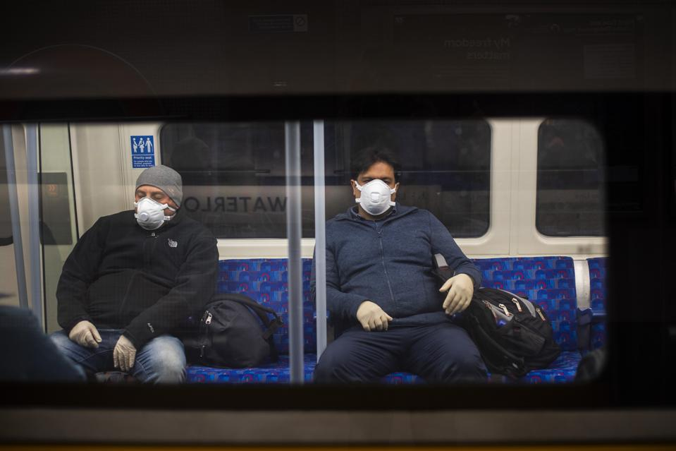 Two men wear face masks on the London Underground Jubilee line during lockdown.
