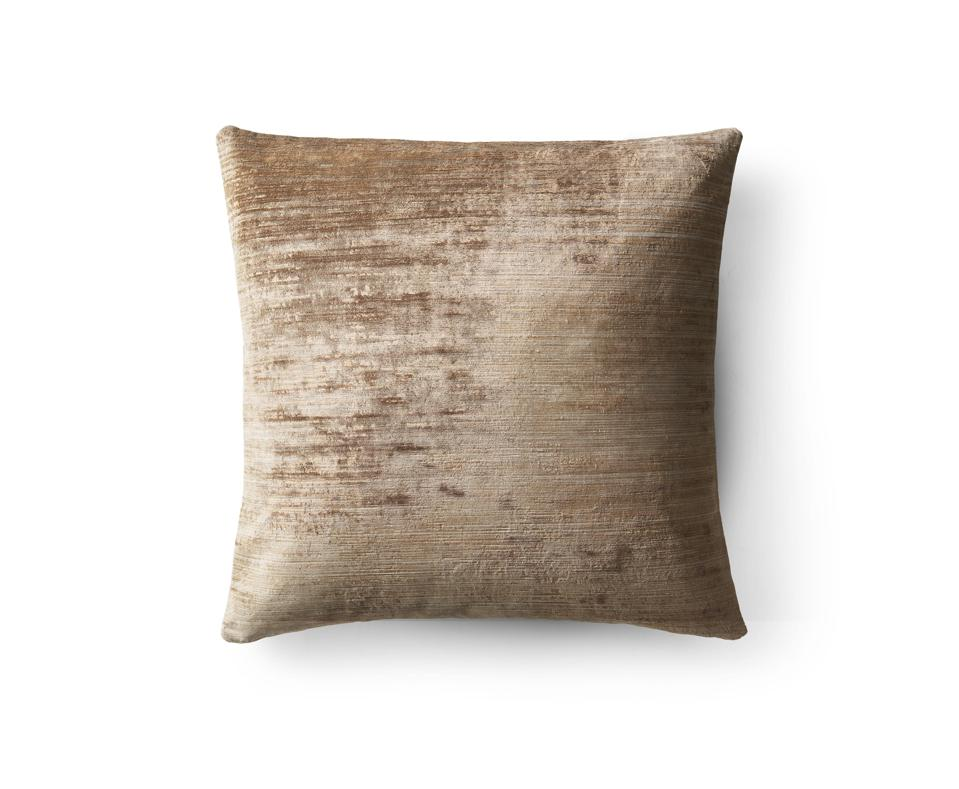 A brushstroke velvet pillow in a copper hue.