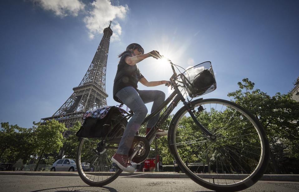 A cyclist rides past the Eiffel Tower on a sunny day in Paris.