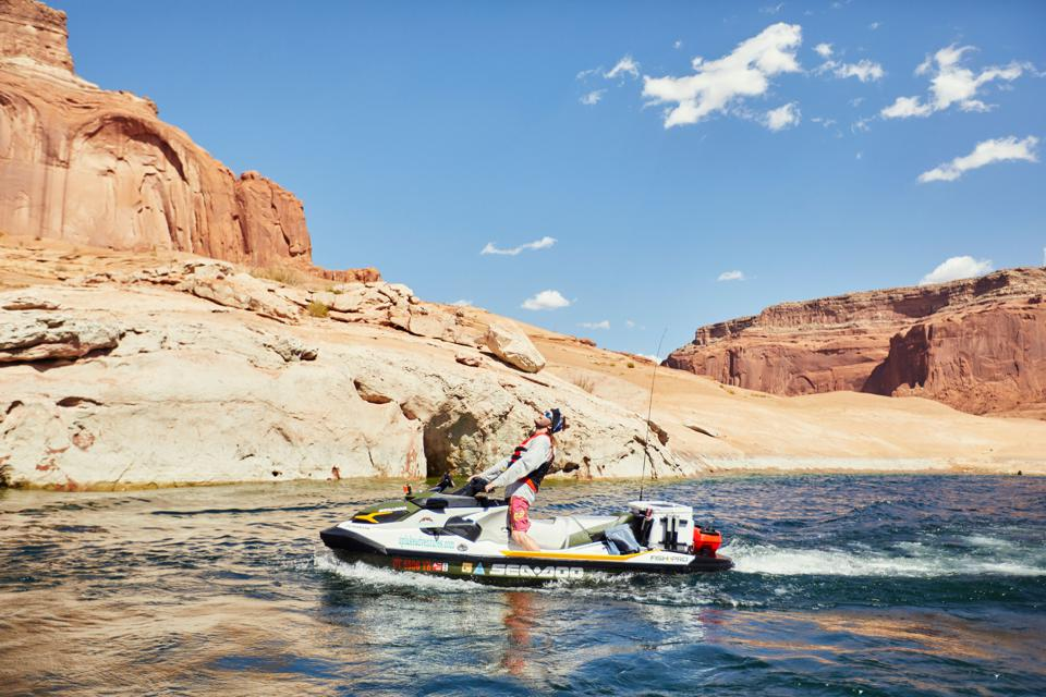 A young man screams on top of a Sea Doo in a desert lake.