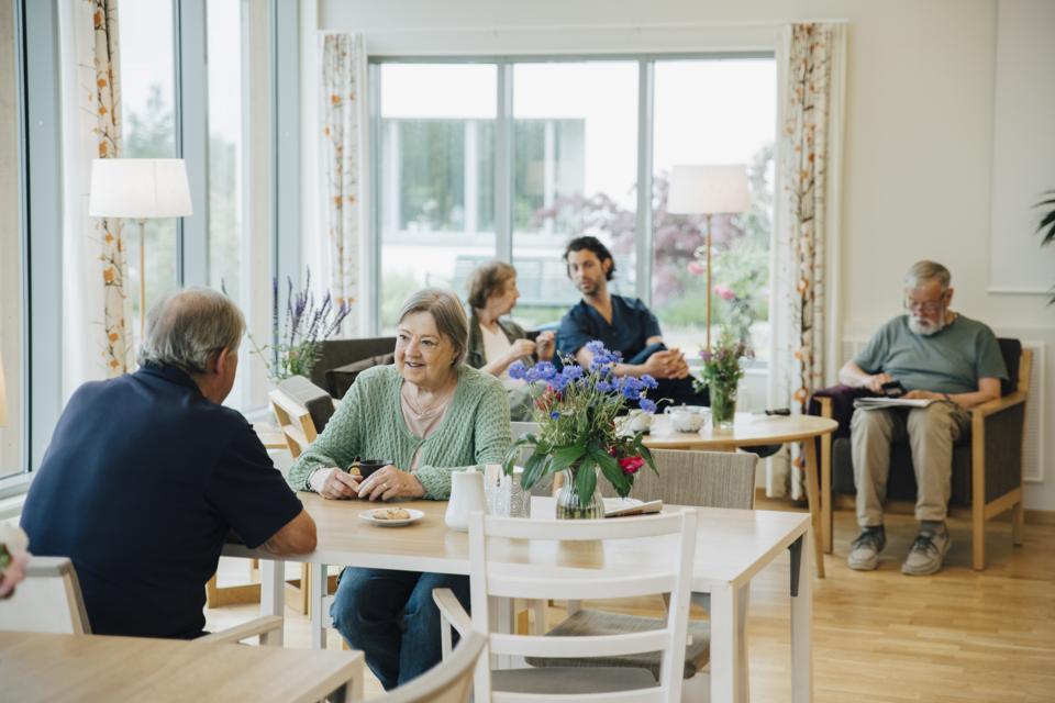 Retired senior men and women sitting with male nurse at elderly nursing home
