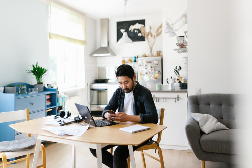 Asian man using smart phone while working from home