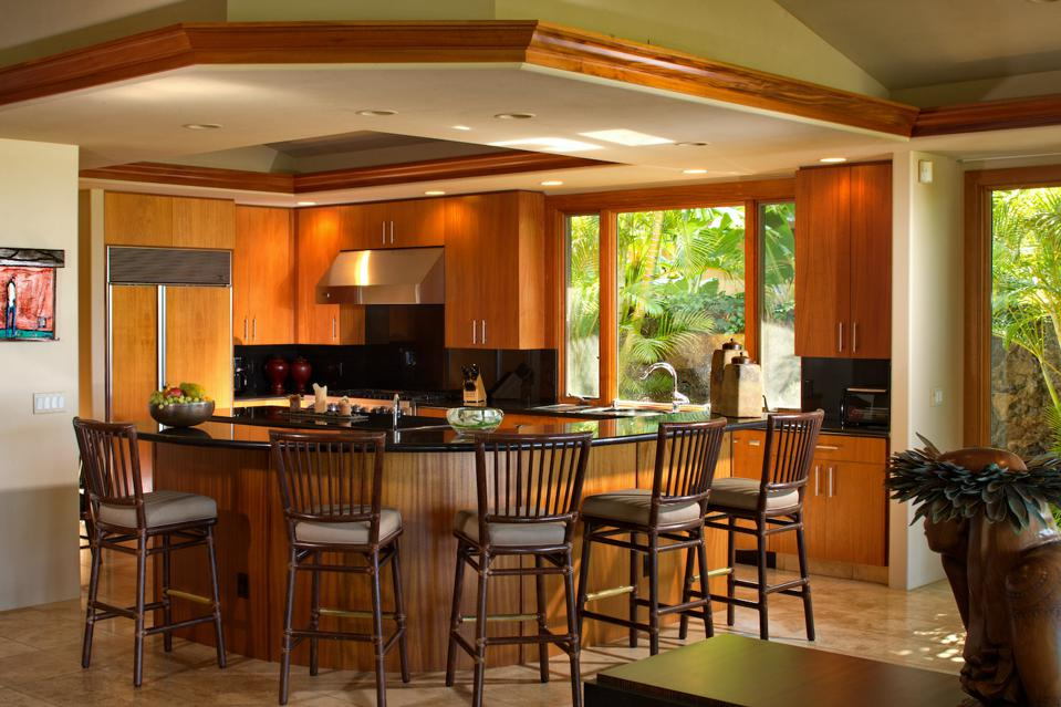 The kitchen features rich mahogany cabinetry, sleek countertops, high-end appliances, bar seating and a built-in office desk.