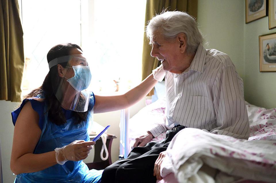 Hold Still Photo Exhibit: a care worker visiting a patient during the pandemic.