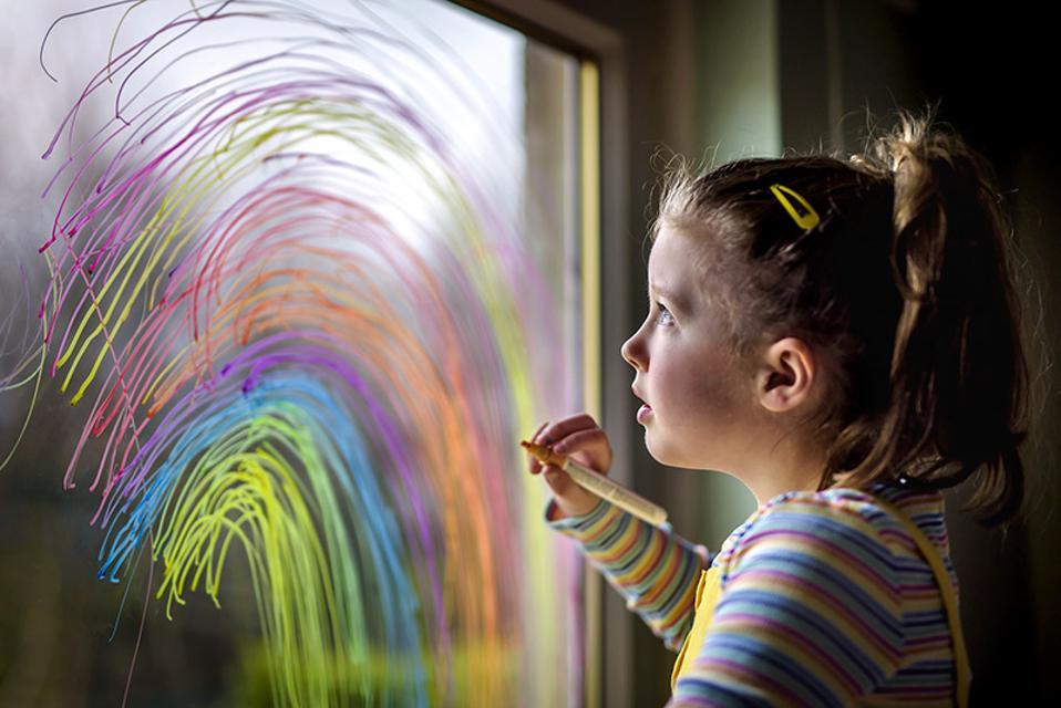 Hols Still; a girl painting a rainbow on a window