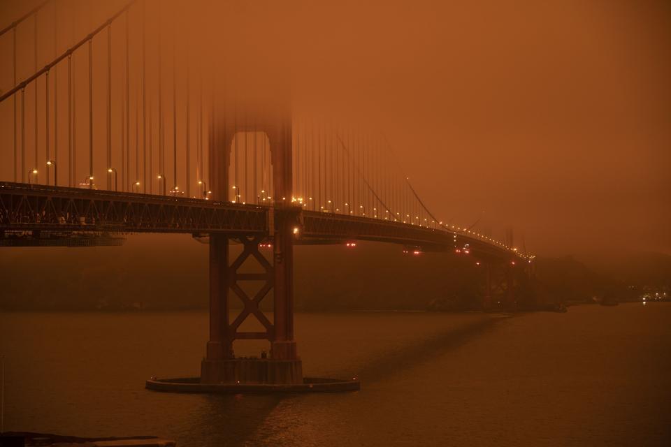Golden Gate bridge shrouded in orange haze from wildfire smoke and ash