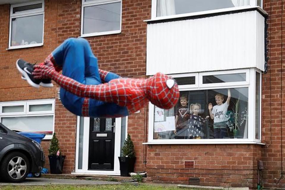 Hold Still photo exhibit, a Spiderman entertaining kids