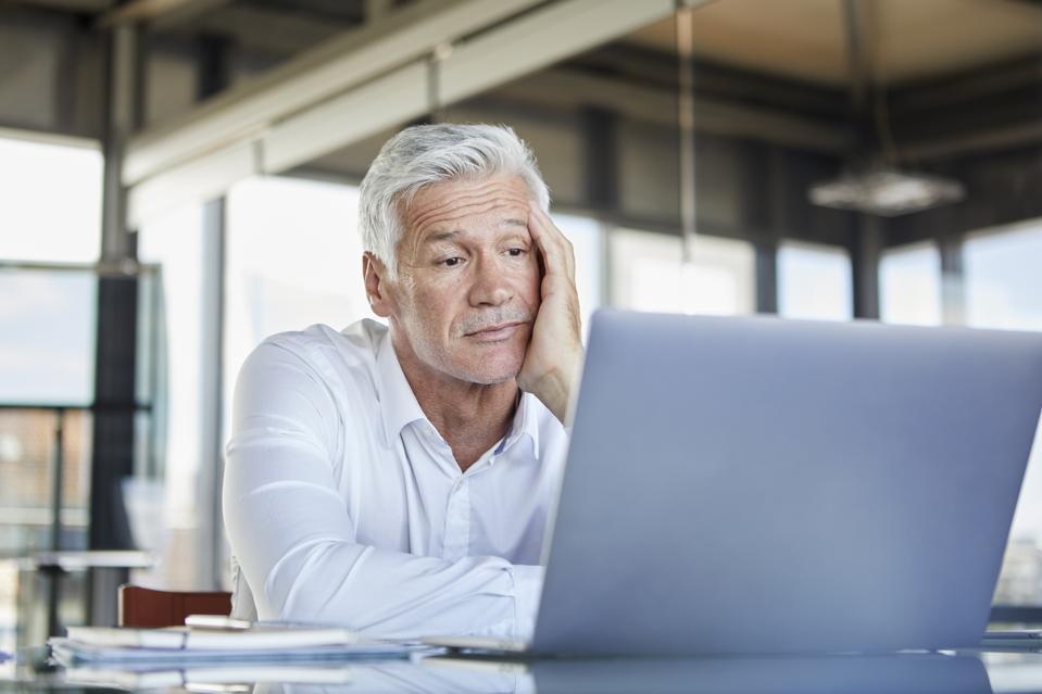 Bored businessman sitting at desk, using laptop